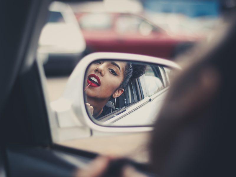 Mulher se maquiando pelo retrovisor