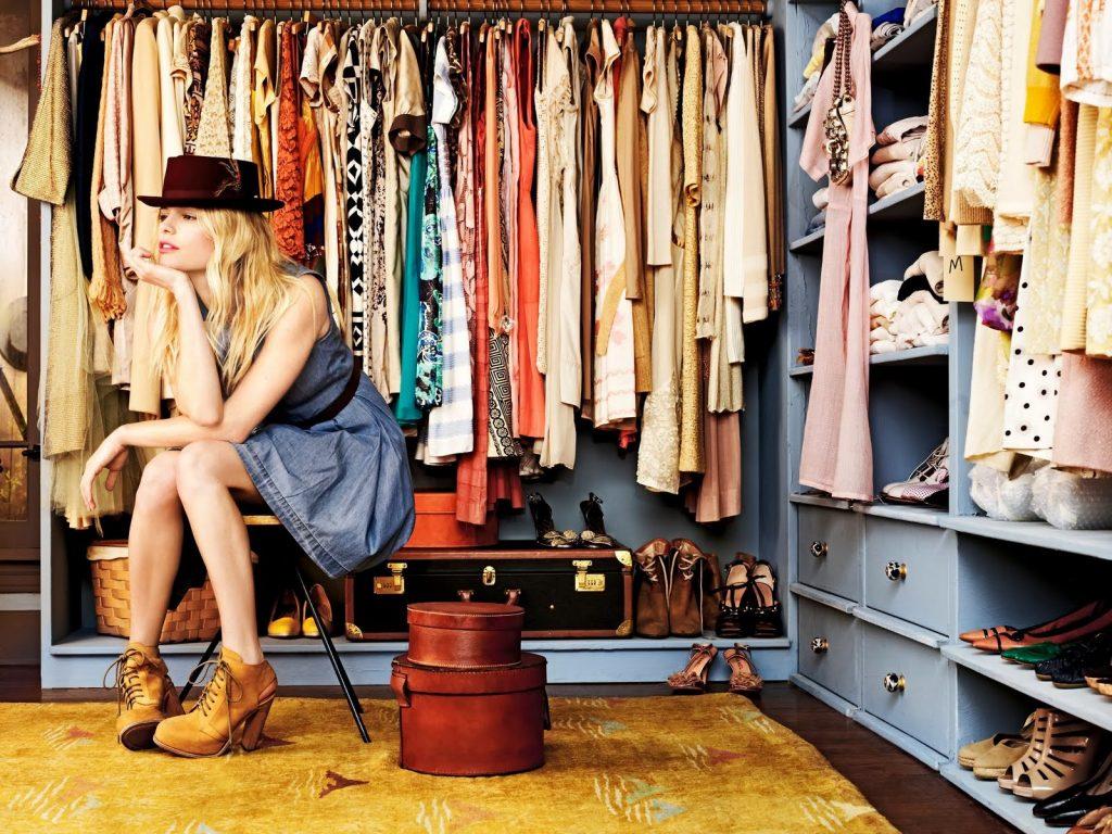 Mulher sentada no guarda roupa com cara de perdida