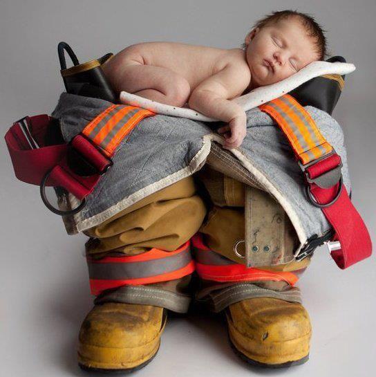 Bebê deitado em roupa de bombeiro