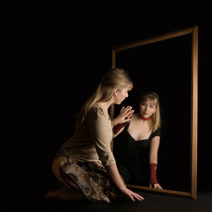 Mulher de frente pro espelho. Imagem refletida é diferente da real.