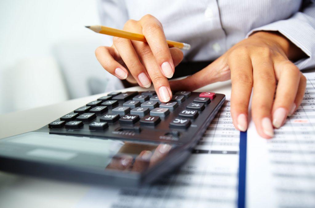 Mão de uma mulher segurando lápis e usando uma calculadora