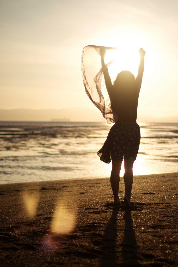 Mulher na praia de braços abertos para o nascer do sol
